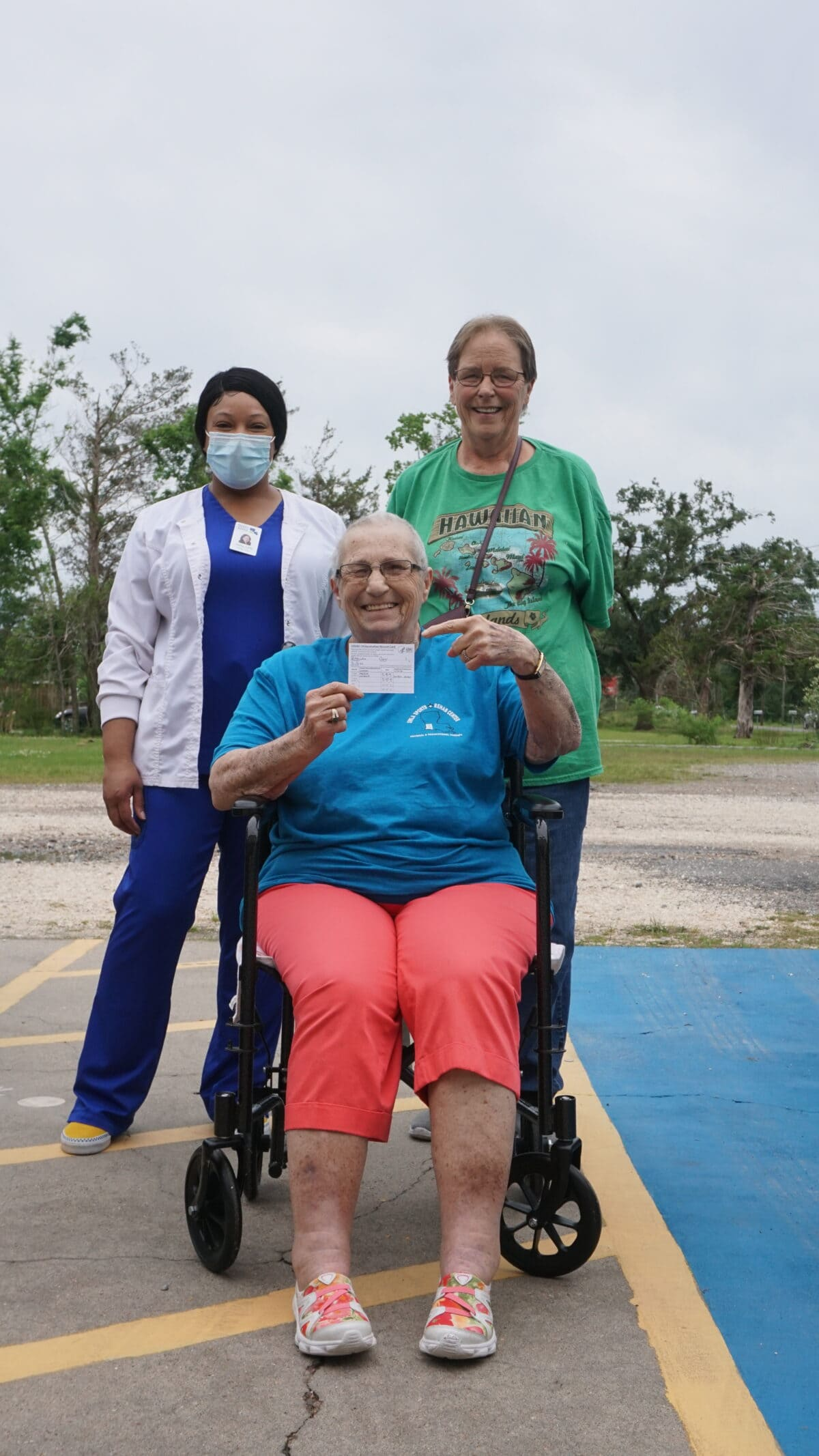 Carol Pettyjean, seated, shows off her vaccination card after getting her shot.